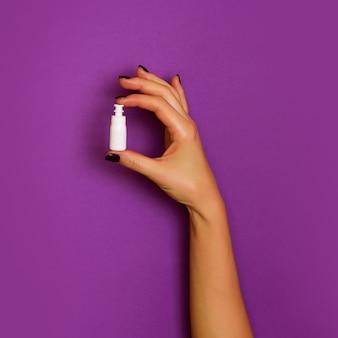 보라색 배경에 흰색 화장품 병을 들고 여성 손
