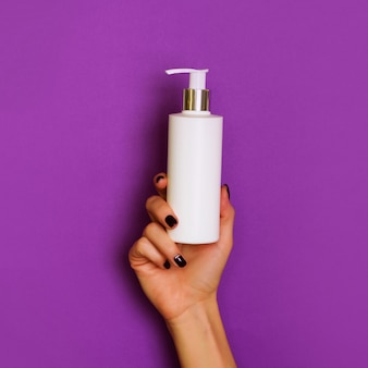 Female hands holding white cosmetic bottle on violet background