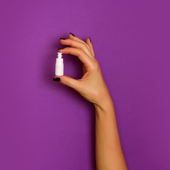Female hands holding white cosmetic bottle on violet background.