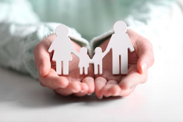 흰색 가족 인물을 들고 여성 손