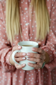 Female hands holding a white mug with beverage. close up. blurred background