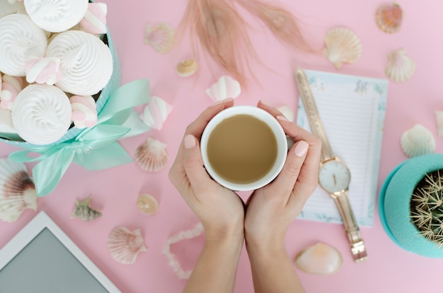 Female hands holding a white mug with beverage on pastel pink background.