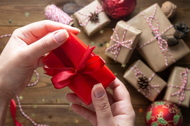 Female hands holding, wrapping christmas gift box. group of gift boxes wraped in craft paper, red baubles, glitter over wooden tables. chritsmas flat lay background.