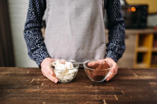 Женские руки держат миски с шоколадом и маслом