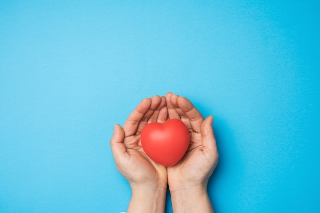 Female hands holds red textile heart, blue background. love and donation concept, close up