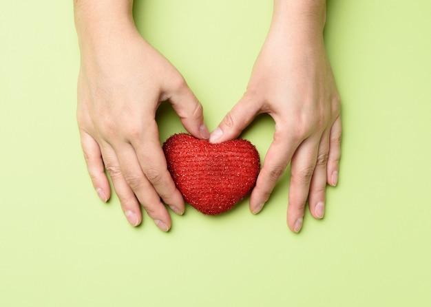 女性の手は赤い織物の心を保持します愛と寄付
