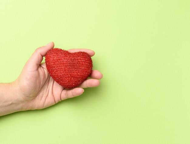 女性の手は赤い繊維の心を保持します