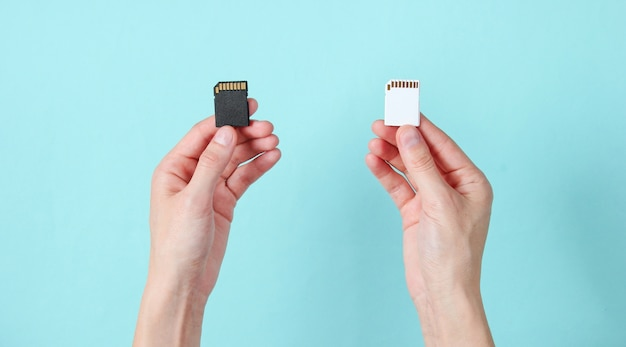 Female hands holds two sd memory cards on blue. minimalist techno concept.