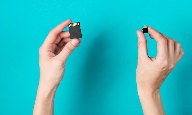 Женские руки держит две карты памяти sd на синем. минималистская техно-концепция.