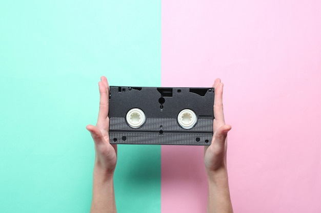 Female hands holds video cassette on pink blue pastel background. retro style, pop culture, minimalism, top view