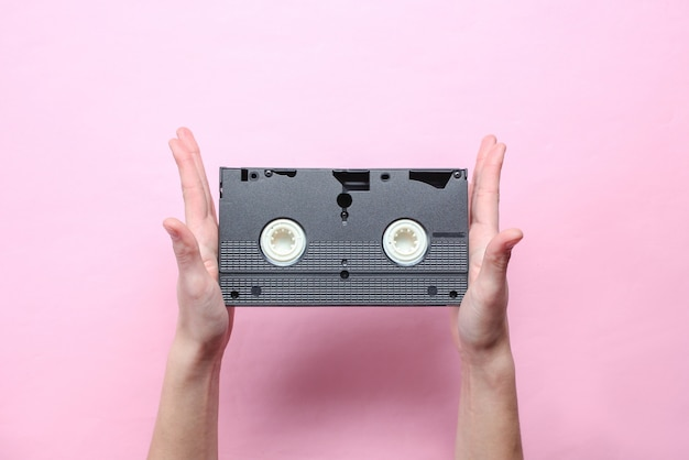 Female hands holds video cassette on pink pastel background. retro style, pop culture, minimalism, top view