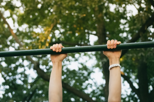 Female hands on the horizontal bar outdoors in the park