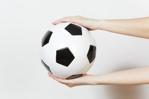여성 손 수평 흰색 배경에 고립 된 축구 클래식 흰색 검은 공을 들고. 스포츠, 축구, 건강, 건강한 라이프 스타일 개념을 재생합니다.