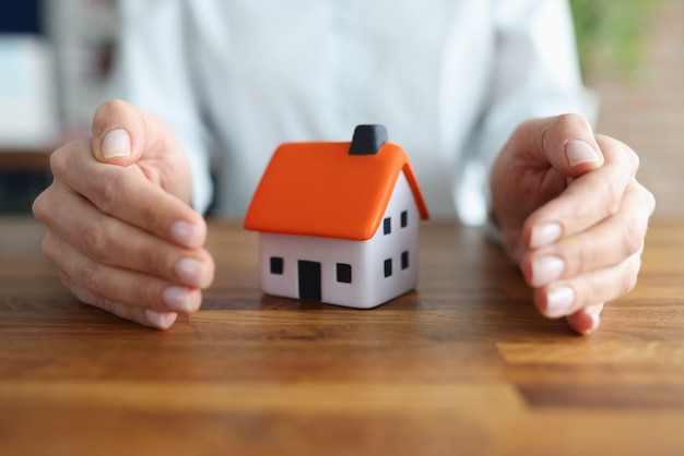 Female hands hugging small toy house closeup