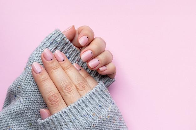 トレンディな美しいマニキュアと灰色のニットセーターの女性の手-コピースペースとピンクの背景に黒い小さな点を持つピンクの裸の爪