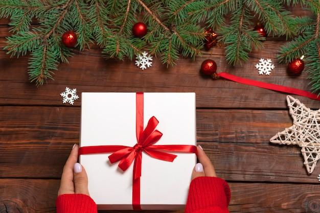 Женские руки в красном новогоднем свитере, держа белую подарочную коробку на коричневом деревянном фоне