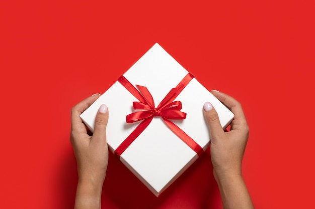 Женские руки в красном новогоднем свитере, держа белую подарочную коробку на красном фоне минимализма
