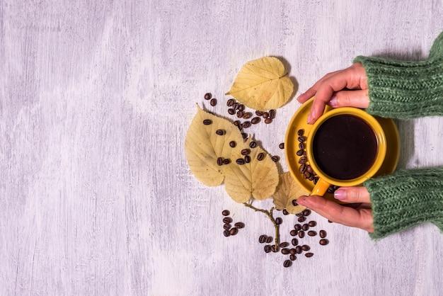 暖かいセーターの女性の手は、軽い素朴な木製のテーブルにコーヒーを保持します。