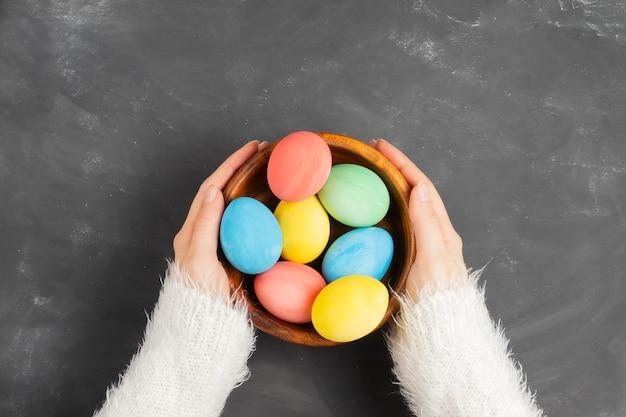 하얀 솜털 스웨터에 여성의 손은 염색 된 다채로운 부활절 달걀로 나무 에코 플레이트를 잡고