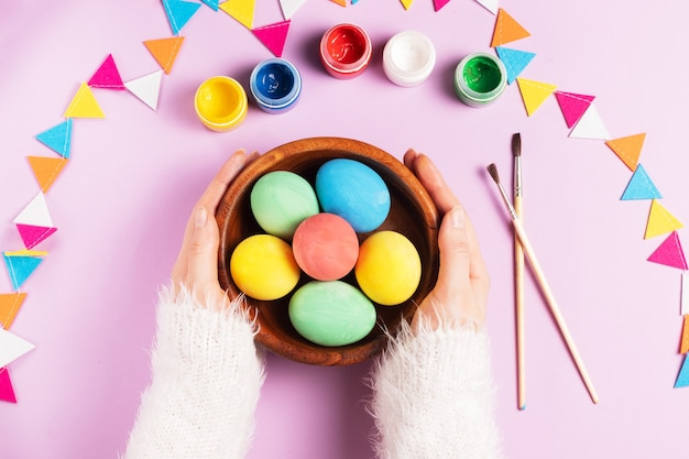 白いふわふわのセーターの女性の手は、ペイントでピンクの背景にカラフルなイースターの卵と木の板を保持します。