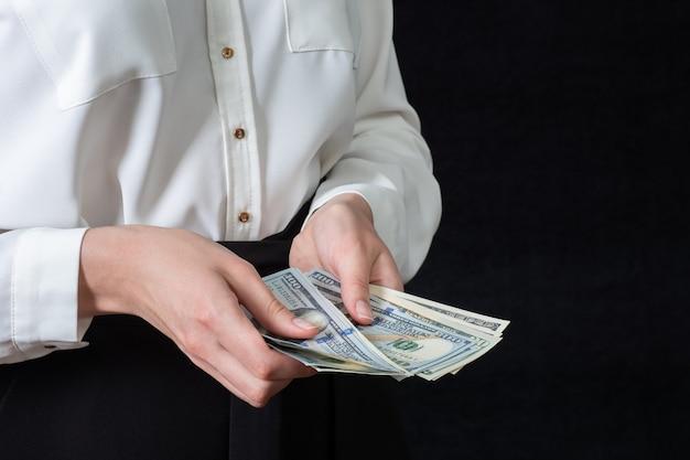 흰 셔츠를 입은 여성의 손은 수백 달러 지폐를 들고 있고, 돈을 세고, 검은 배경, 복사 공간, 클로즈업에 격리되어 있습니다. 사업 개념, 투자, 저축