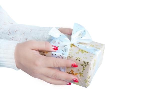 Женские руки в белом свитере протягивают подарочную коробку.