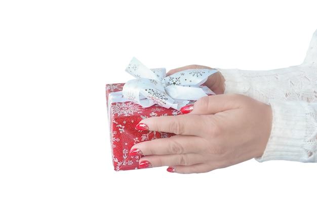 Женские руки в белом свитере протягивают красную подарочную коробку с белым бантом.