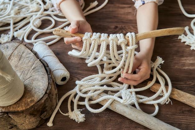 マクラメの装飾を作る方法を示すワークスペースの女性の手