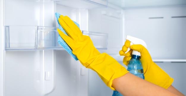 Женские руки в желтой резиновой защитной перчатке и синей губке моют, чистят полки холодильника.