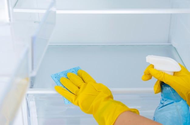노란색 고무 보호 장갑과 파란색 스폰지에 여성의 손을 씻고 냉장고 선반을 청소합니다.