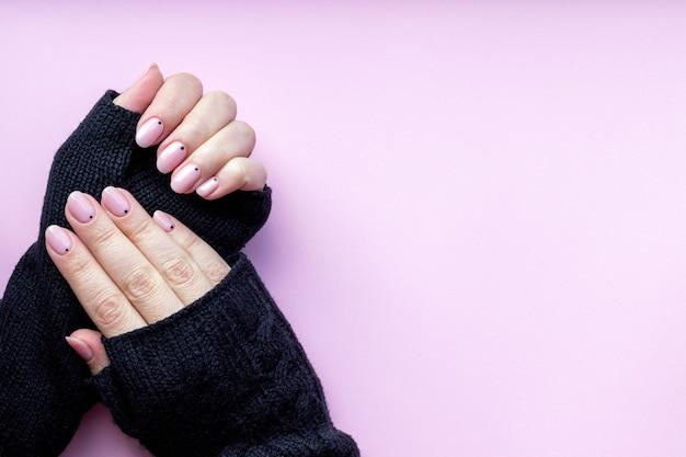 トレンディな美しいマニキュアと黒のニット手袋ミットの女性の手