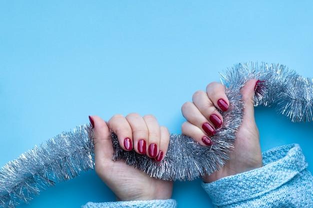美しい光沢のあるマニキュアと青いニットセーターの女性の手