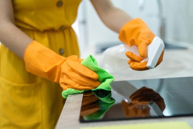 黒い台所の表面を掃除する手袋の女性の手。家庭のコンセプト