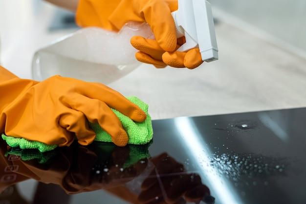 黒い台所の表面を掃除する手袋の女性の手。家庭のコンセプト Premium写真