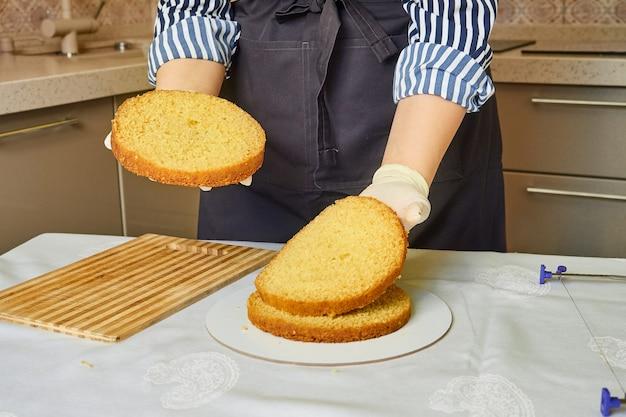 手袋をはめた女性の手は、ケーキの完成した層を折ります