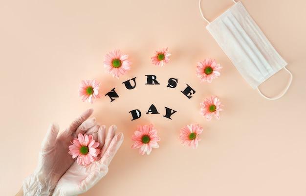 手袋をはめた女性の手は、白い医療とパステルピンクの背景にピンクの菊を保持します。