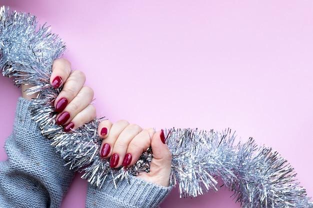 光沢のあるマニキュアとグレーのニットセーターの女性の手