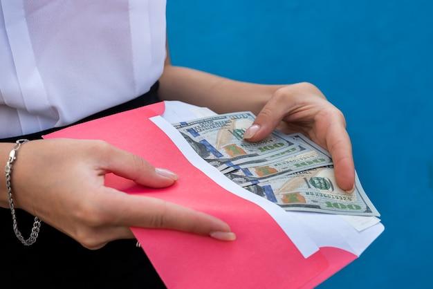 Женские руки в наручниках, держа конверт с долларами. понятие коррупции и взяточничества
