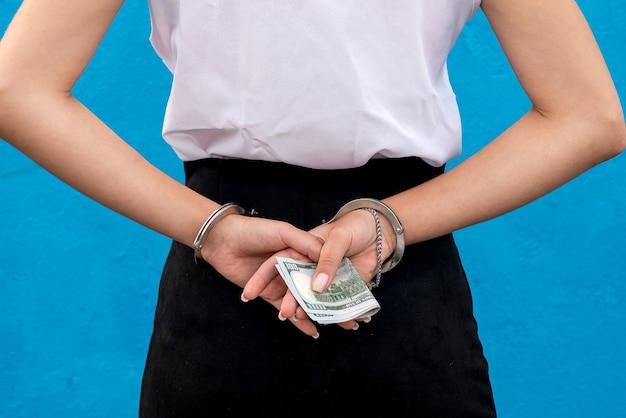 수갑을 찬 여성의 손은 우리에게 돈을 쥐고 있습니다. 불법 사업의 개념., 부패