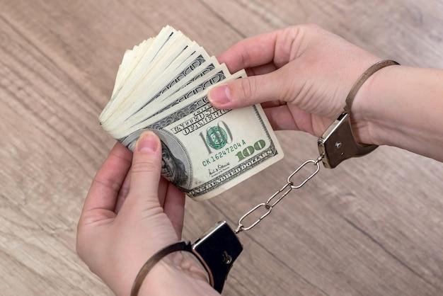 テーブルの上にドルと手錠で女性の手