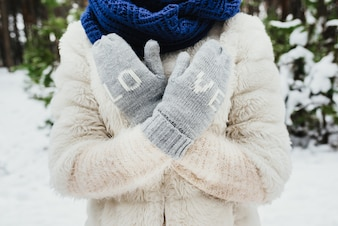 Female hands in knitted mittens. On mittens embroidered with the word love.