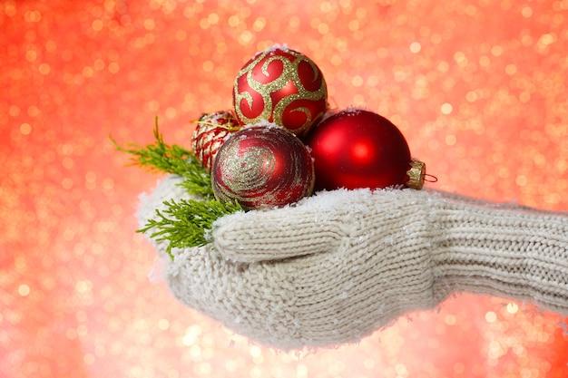 色の背景に、ミトンのクリスマスツリーボールの女性の手