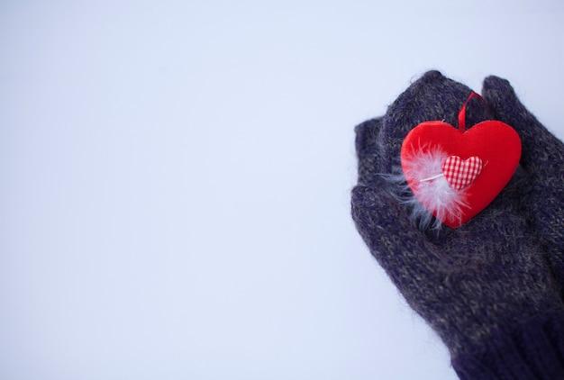 붉은 마음으로 장갑에 여성 손 클로즈업