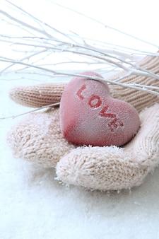 Женские руки в рукавицах с красным сердцем, крупным планом
