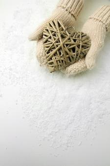 枝編み細工品の心を持つミトンの女性の手、クローズアップ