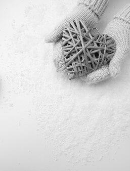 Женские руки в рукавицах с плетеным сердцем, крупным планом