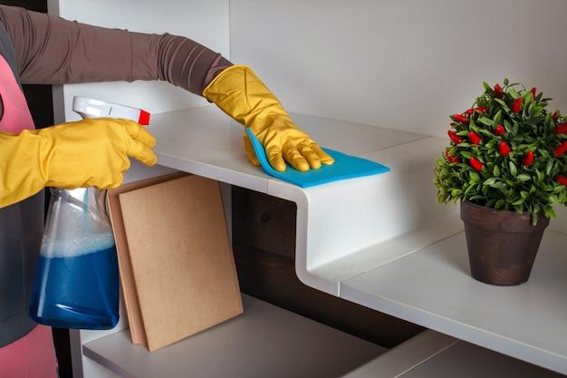 Женские руки в резиновых перчатках моют полку спреем.