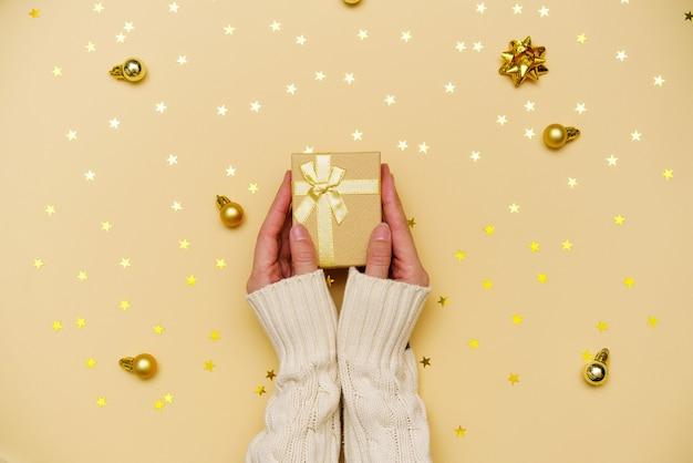 Женские руки в свитере держат подарочную или подарочную коробку, украшенную конфетти и елочными шарами на желт ...