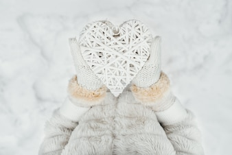 Female hands in white knitted mittens with a entwined vintage romantic white heart