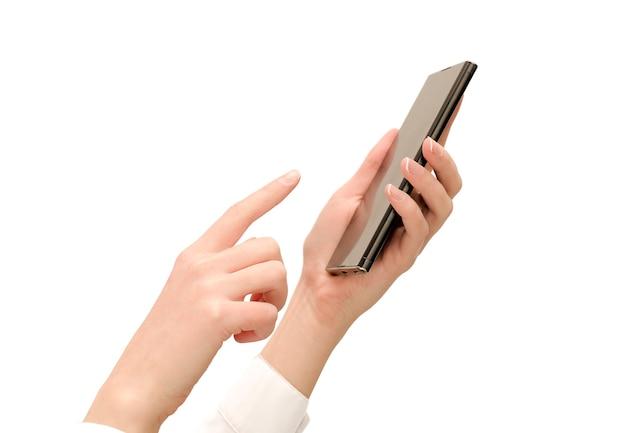 孤立した白い壁にスマートフォンと白いシャツの女性の手